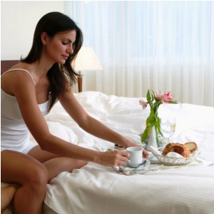 Side profile of a young woman having breakfast in bed